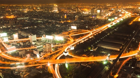 expressway: Busy road intersection in the heart of downtown Bangkok, shot at night showing car headlight trails Stock Photo