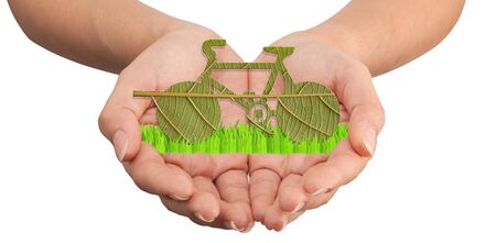 toxic emissions: Hands holding leaf bicycle for green concept