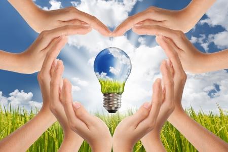 eficiencia energetica: Ahorro, bulbo Global concepto de energ�a soluciones con luz verde y planeta brillante panorama de manos