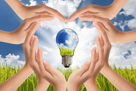 global innovation: Hands saving , Global Concept of Green Energy Solutions With Light bulb and Planet on Bright Landscape Stock Photo