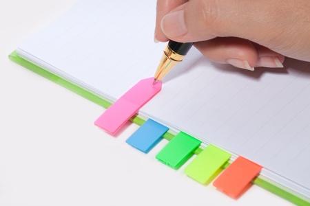 book binding: Female hand writing bookmark on notebook