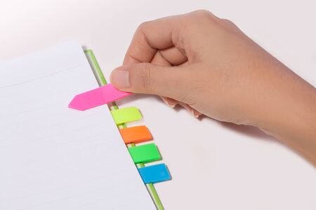 Female hand past bookmark on notebook Stock Photo - 10849447