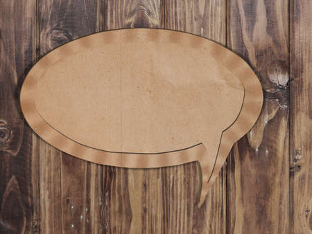 Blank Recycle paper Speech Bubble on wood background photo