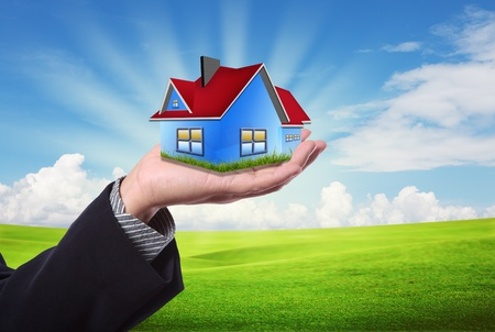 house in hand: The House in the hands against the blue sky as a symbol of the real estate business.