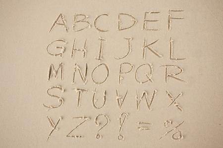 sandy: El alfabeto escrito en la arena en una playa.