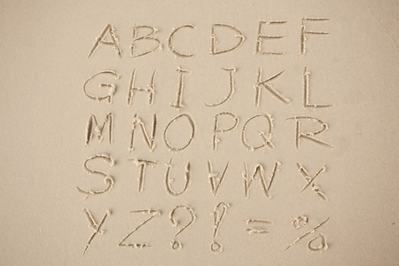 sand drawing: The alphabet written in sand on a beach.