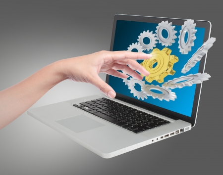 hand pushing on a touch gear on notebook screen photo