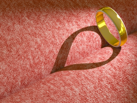 Wedding ring casting a heart on pink cloth photo