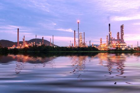 green grass field with scenic of petrochemical oil refinery plant shines at night  photo