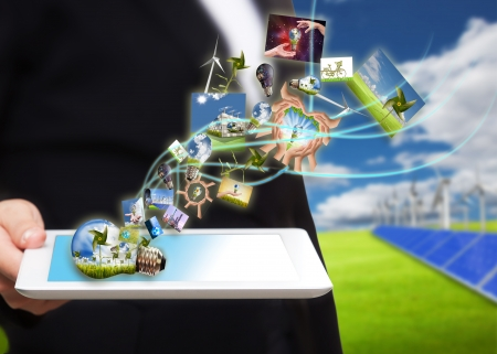 saving energy stream images from tablet pc on the field with solar cell and wind turbine  photo