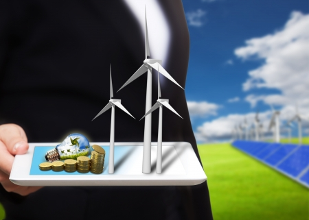 saving energy stream images from tablet pc on the field with solar cell and wind turbine Stock Photo - 16459881