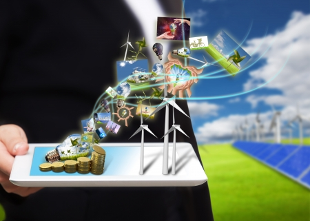 energy save: saving energy stream images from tablet pc on the field with solar cell and wind turbine  Stock Photo