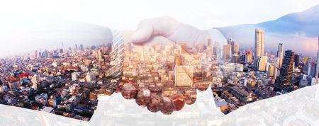都市の背景に二重露光握手ビジネスマン