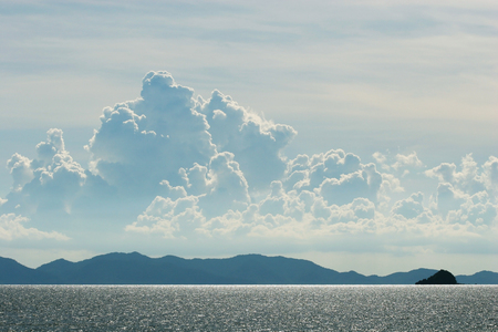 Landscape light reflected from the surface of the sea. Beautiful clouds and mountains, far away. photo