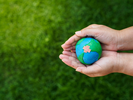 earth in hands and green grass field background. environment save earth concept. Stock Photo