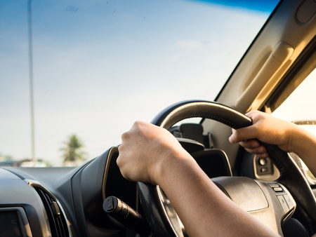 Man's hands holding steering wheel and road background. Driving concept