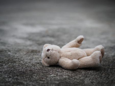 El oso de peluche está acostado en el suelo. concepto solitario. día internacional de los niños desaparecidos.