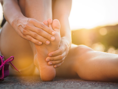 Running injury leg accident- sport woman runner hurting holding painful sprained ankle in pain. Female athlete with joint or muscle soreness and problem feeling ache in her lower body. Stock Photo