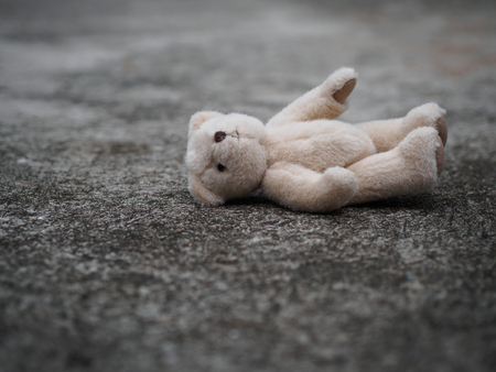 Teddy bear is laying down on the floor. lonely concept. international missing children's day.