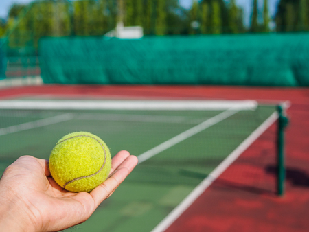 Close up of tennis ball on the hand at the tennis court. Sport active concept.