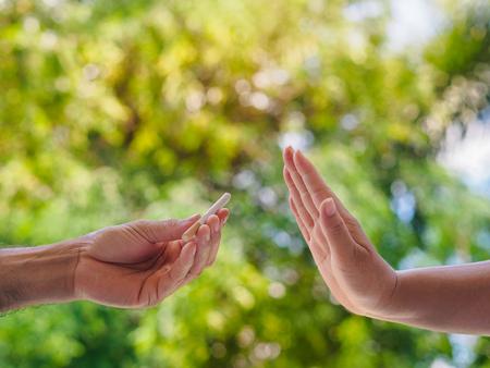 Rauchen verboten. Schließen Sie oben von den männlichen Händen, die Zigaretten halten und es der Person vorschlagen. Der menschliche Arm zeigt mit Ablehnung auf Bokeh-Hintergrund. Standard-Bild