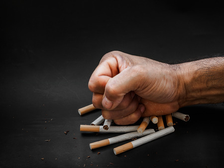 Man hand punching and destroy cigarettes on black background. Quitting smoking concept. world no tobacco day