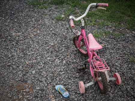 Children's bikecycle and shoe on stone road. missing children concept. international missing children's day.