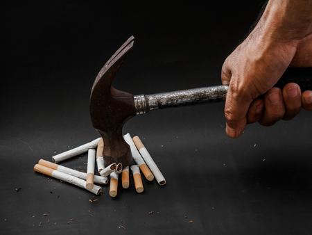 Hammer schlagen und Zigaretten auf schwarzem Hintergrund zerstören. Raucherentwöhnungskonzept. Welt kein Tabak Tag