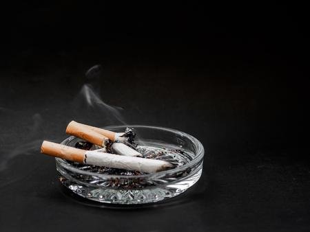 Cigarette in the ashtray on a black background. TOBACCO.