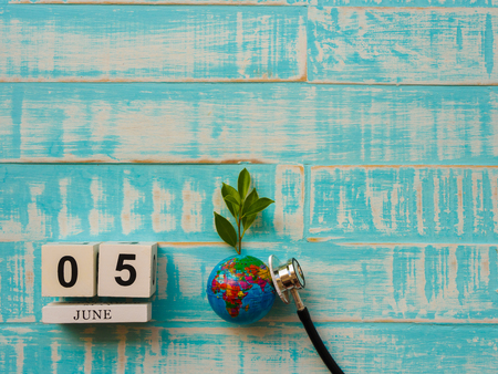 05 JUNE wooden block calendar globe and stethoscope on blue wooden background. Stock Photo