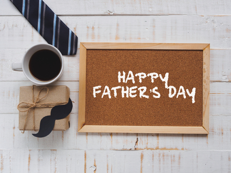 Happy fathers day concept. 17 June wooden block calendar, tie, board with HAPPY FATHERS DAY text and a cup of coffee on white wooden background.