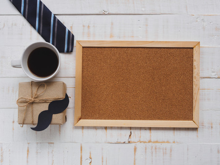 Happy father's day concept. 17 June wooden block calendar, tie, board and a cup of coffee on white wooden background.