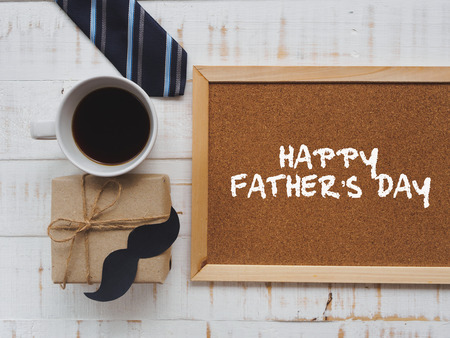 Happy father's day concept. 17 June wooden block calendar, tie, board with HAPPY FATHER'S DAY text and a cup of coffee on white wooden background. Stockfoto