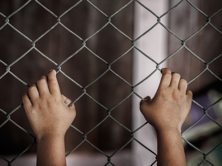 little girl hand holding on chain link fence for freedom, Human Rights Day, child labor, violence concept. Stock fotó