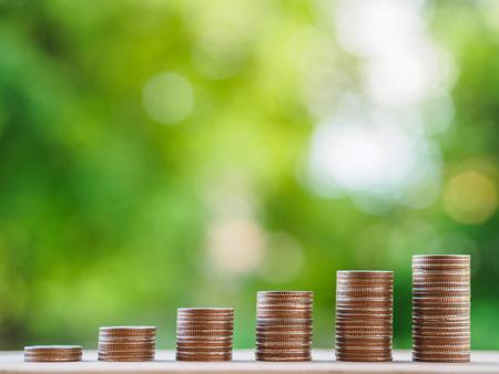 Risparmio di denaro concetto. concetto di business in crescita. pila di monete di denaro sul tavolo su sfondo bokeh di fondo. Archivio Fotografico