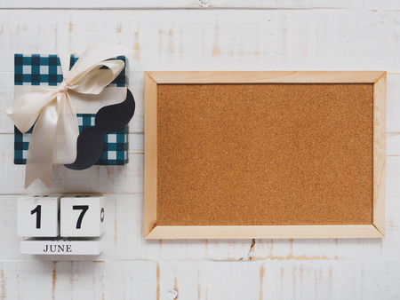 Happy father's day concept. 17 June wooden block calendar, mustache,  gift box and board on white wooden background.