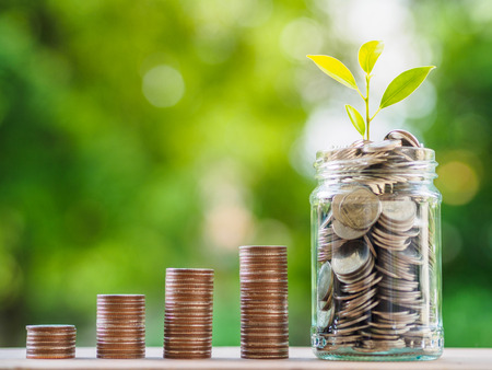 Risparmio di denaro concetto. concetto di business in crescita. pila di monete di denaro sul tavolo su sfondo bokeh di fondo.
