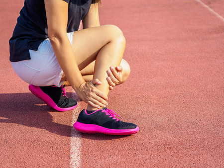 Athlete woman has ankle injury, sprained leg during running training. sport concept.