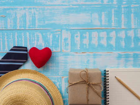 Happy Father's Day inscription with gift box, redheart, hat, necktie, notebook and pencil on blue wooden background. father's day concept. Banco de Imagens