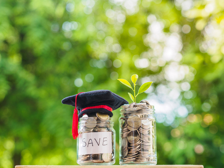 Ahorrar dinero para el concepto de educación. Monedas en frasco de vidrio con sombrero de posgrado sobre fondo borroso.