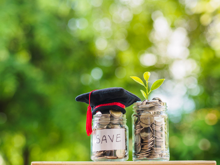 Saving money for education concept. Coins in glass jar with graduate hat on blur background.