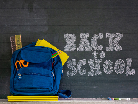 Back to school concept. School bag with stationery and notebooks in front of blackboard. Stock Photo