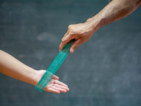 l'enseignant utilise la règle pour frapper la main de l'enfant pour le punir. Banque d'images