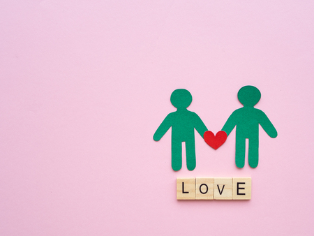 Male couple paper with red heart and LOVE text wooden block on pink background. Love, LGBT, gay pride, homosexual, valentines day concept.