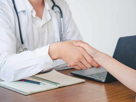Doctor and Patient are shaking hand in the hospital. Health care and Medical Concept. 版權商用圖片