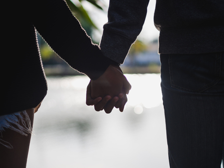 Couple holding hands beside the lake blurred background. Love & Go together Concept 版權商用圖片