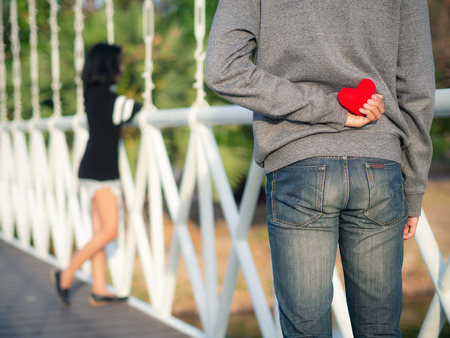 Man hiding red heart behind his back for his girlfriend. Love, Valentines Day Concept. 版權商用圖片