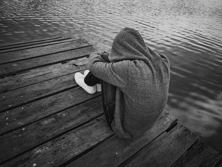 Black and White The man sitting on a pier beside the lake. Alone, lonely, sad Concept.