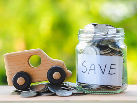 close up jar of coins and toy car on wooden table on blur background, saving money for car  and business concept