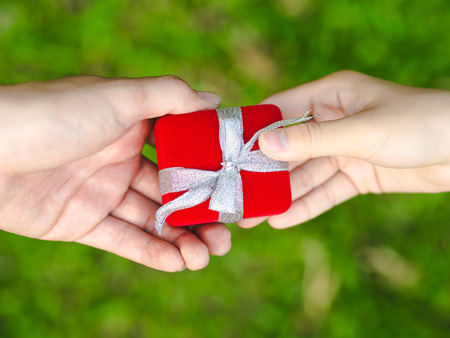 Man giving a red gift box to woman. Love, Valentine,Present Concept.